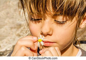 Beautiful little girl playing with flower.
