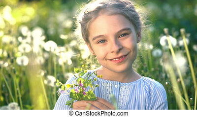 Beautiful little girl playing with flowers at summer day. -...