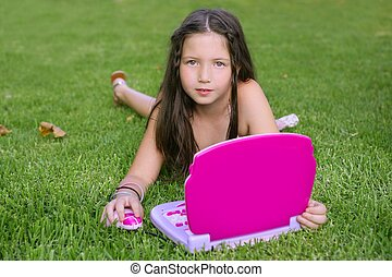 Beautiful little girl playing with pink toy computer