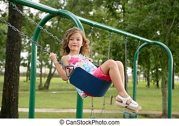 Beautiful little girl playing with swing