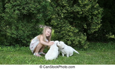Beautiful little girl playing with the puppies in nature