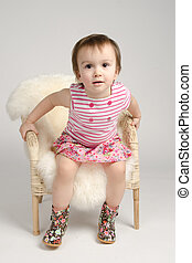 Beautiful little girl posing with armchair