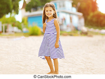 Beautiful little girl resting on the beach