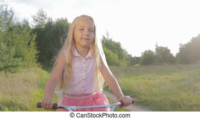 Beautiful, little girl rides a children's bike, kids bicycle