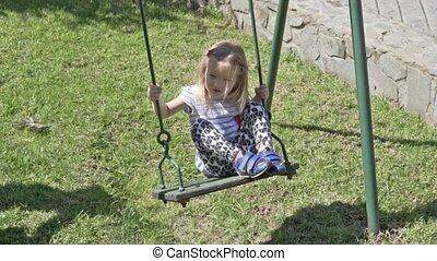 Beautiful little girl riding a swing in the park