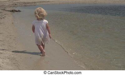 Beautiful little girl runs along the seashore. Little girl in a white dress on the coast. Slow motion.