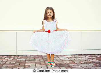 Beautiful little girl shows white dress outdoors against the urban wall