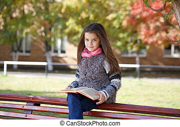 Beautiful little girl sitting on a bench