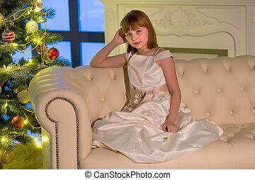 Beautiful little girl sitting on a sofa near the New Year tree.
