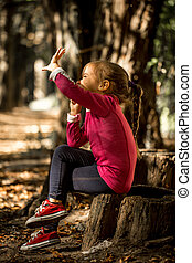 beautiful little girl sitting on a stump in the woods