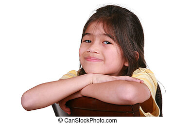 Beautiful little girl sitting on chair smiling