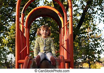 beautiful little girl sitting on playground slide