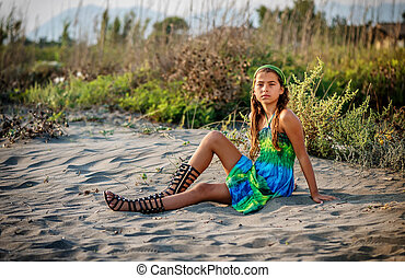 Beautiful little girl sitting on the beach