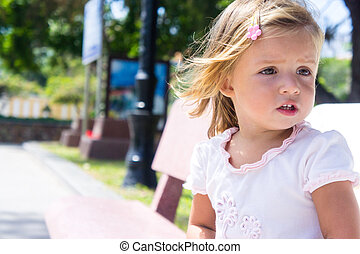 beautiful little girl sitting on the bench