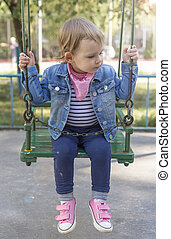 girl sitting securely chained on a swing