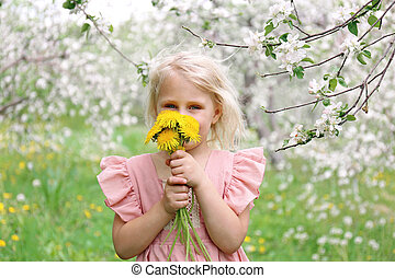 Beautiful Little Girl Smelling Flowers Outside in Under the Apple Trees