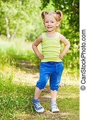 Beautiful little girl standing on a path in park