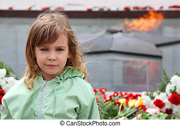 beautiful little girl stands near memorial, eternal flame, flowers