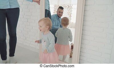 Beautiful little girl stay near the mirror with her family...