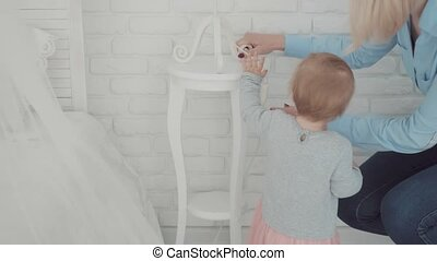 Beautiful little girl stay near the table and lamp with mother. Slow Motion. Baby milestone, toddler, 1 year old. Happy childhood