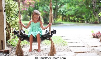 beautiful little girl swinging on a swing in a cozy lovely flowered courtyard