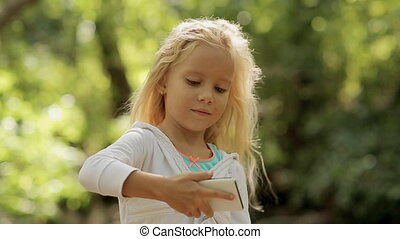 Beautiful little girl takes pictures on the phone in the forest