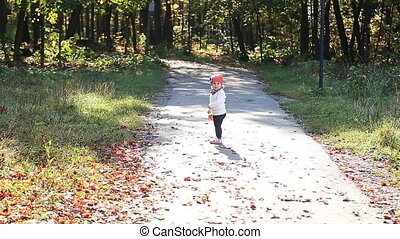 Beautiful little girl throws up yellow autumn leaves in the park