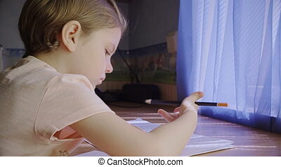Beautiful little girl uses an eraser at home