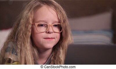 Beautiful little girl using computer in bedroom