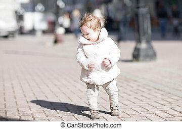 Beautiful little girl walking in the sun