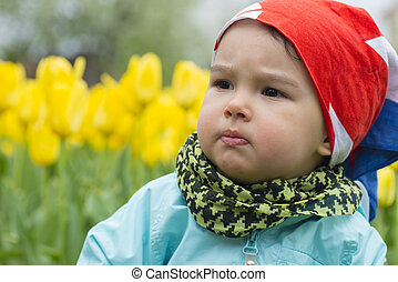 Beautiful little girl with a field of tulips in background