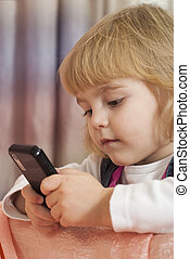 Beautiful little girl with a phone in their hands