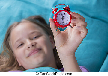 Beautiful little girl with alarm clock on bed in the bedroom.