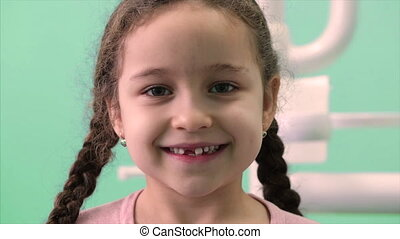 Beautiful Little Girl With Curly Hair and Two Pigtails in the Dental Chair Smiles and Looks at the Camera to Show Where She lost a Few Teeth.