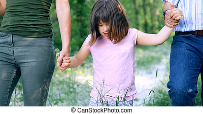 Beautiful little girl with down syndrome walking with parents