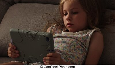 Beautiful little girl with gadget in bed at night. Bedtime...