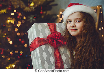 eautiful little girl with gift and in Santa hat.