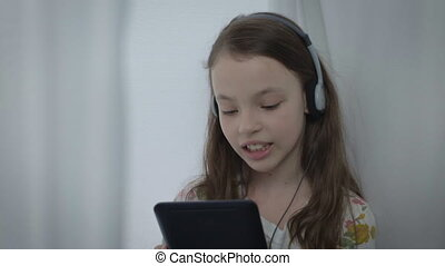 Beautiful little girl with headphones watching a music video on the tablet and sings.
