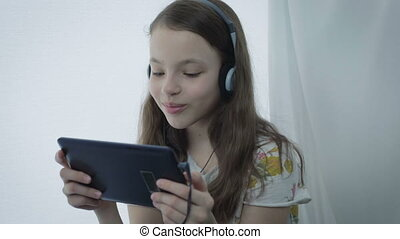 Beautiful little girl with headphones watching funny videos on tablet