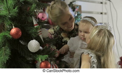 Beautiful little girl with her mother and younger sister decorating a Christmas tree