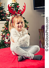 Beautiful little girl with horns, sitting beside christmass tree and smiling
