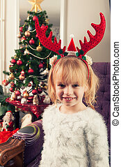 Beautiful little girl with horns, standing beside christmass tree and smiling