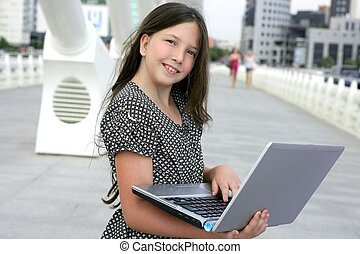Beautiful little girl with laptop computer