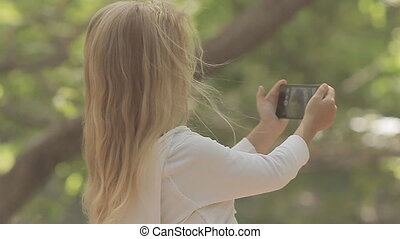 Beautiful little girl with long blond hair photographing herself on phone