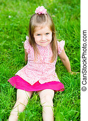 Beautiful little girl with long blond hair, sitting on grass