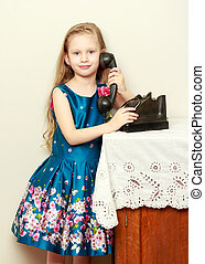 Beautiful little girl with long blond hair, holds the ear of an