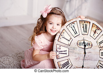 Beautiful little girl with long curly hair in pink dress with a big clock waiting for the new year