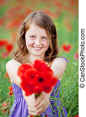 Beautiful little girl with red flowers