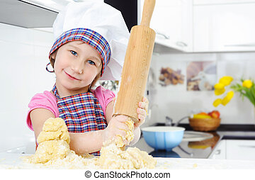 Beautiful little girl with rolling pin