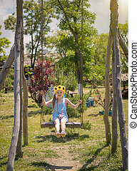 Beautiful little girl with sunflowers on the head swinging on an old swing high.